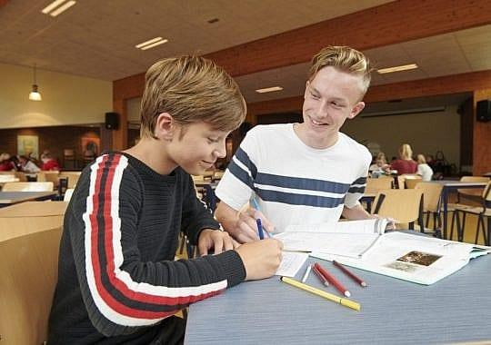 leerling begeleidt 1e jaars bij huiswerk